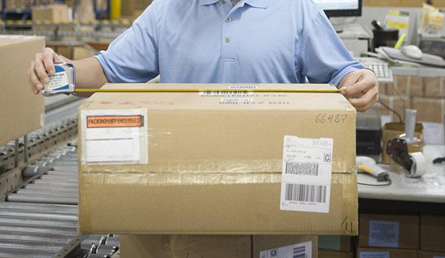 Person som mäter ett paket på vårt 3PL-lager i Stockholm.