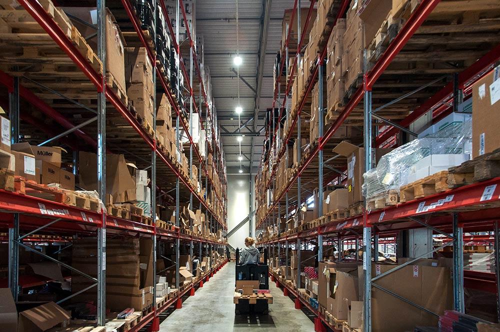 Truckförare på lager fyllt med lagerlådor